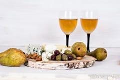 Белое вино и закуски Вино, виноградины, сыр, гайки, оливки Романтичный вечер, натюрморт Стоковая Фотография RF