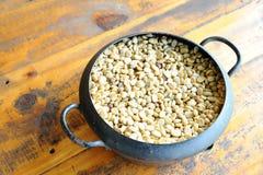 Белое кофейное зерно в винтажном стальном ведре на деревянном столе стоковая фотография