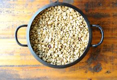 Белое кофейное зерно в винтажном стальном ведре на деревянном столе стоковые изображения