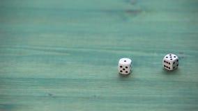 Белое малое dices на деревянной таблице текстуры сток-видео