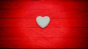 белое сердце на красной деревянной предпосылке нерезкости градиента Стоковая Фотография