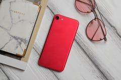 Белое современное desc с красным телефоном, красными стеклами и пасспортом с тетрадью стоковые изображения rf