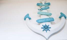 Белое украшение анкера вися на белой стене в доме с пастельными голубыми знаками колеса и пляжа корабля на ем стоковое фото
