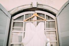 Белое bridal платье на деревянных плечах, против окна Конец-вверх asama Стоковые Изображения