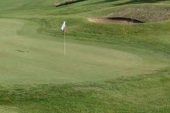 Белое Flagstick в зеленом поле для гольфа в солнечном дне Стоковые Изображения RF