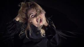 Белокурая ведьма с красными губами сидит на поле, раздражая ее волосы и выкрикивая свирепо, замедленное движение акции видеоматериалы