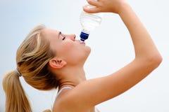 Белокурая девушка выпивает воду стоковые фото
