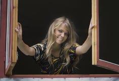 белокурая девушка выходит окно отверстия сь Стоковое Изображение