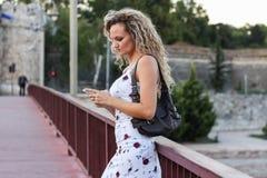 Белокурая девушка в белом платье стоя на мосте и используя a Стоковые Изображения