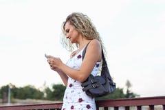 Белокурая девушка в белом платье стоя на мосте и используя a Стоковое Изображение
