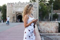 Белокурая девушка в белом платье стоя на мосте и используя a Стоковые Фото