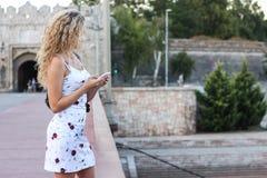 Белокурая девушка в белом платье стоя на мосте и используя a Стоковые Фотографии RF