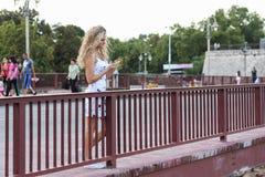 Белокурая девушка в белом платье стоя на мосте и используя a Стоковая Фотография RF