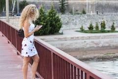 Белокурая девушка в белом платье стоя на мосте и используя a Стоковая Фотография