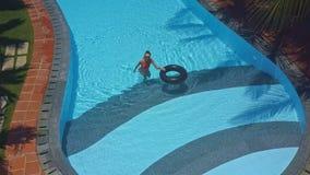 Белокурая девушка в бикини идет из бассейна с кольцом сток-видео