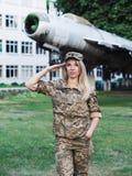 Белокурая девушка в военной форме оставаясь около самолета стоковое фото