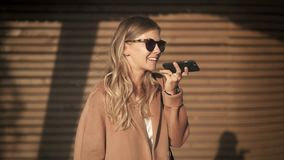 Белокурая девушка в пальто и солнечных очках говоря по телефону в улице осени