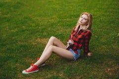 Белокурая девушка в шортах в лете на траве Стоковое фото RF