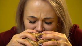 Белокурая девушка есть бургер с мясом и сыром конец вверх акции видеоматериалы