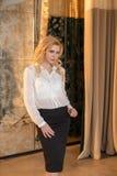 Белокурая девушка одета в одеждах офиса, которая сокращает с ее прозрачностью Блузка белизны, silk и черный строгий стоковое фото