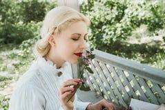 Белокурая девушка пахнуть цветком стоковые фотографии rf