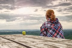 Белокурая девушка сидит самостоятельно на крае над хлябью стоковое фото