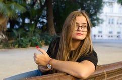 Белокурая девушка со стеклами беседуя со смартфоном стоковое изображение rf