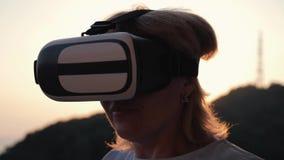Белокурая девушка с стеклами виртуальной реальности на заходе солнца самомоднейшие технологии Виртуальные жизнь и сообщение акции видеоматериалы