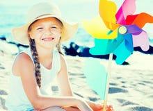 Белокурая девушка с Pinwheel на пляже моря Стоковое фото RF