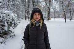 Белокурая девушка усмехаясь в снежном ландшафте стоковое фото