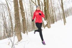 Белокурая женщина бежать outdoors на холодный зимний день стоковое фото