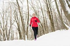 Белокурая женщина бежать outdoors на холодный зимний день стоковая фотография