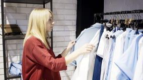 Белокурая женщина выбирая одежды в выставочном зале магазина Стоковое Фото
