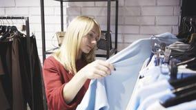 Белокурая женщина выбирая одежды в выставочном зале магазина Стоковые Фотографии RF