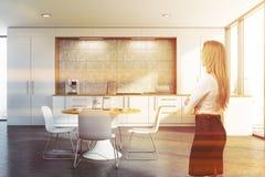 Белокурая женщина в белой кухне стоковые фото