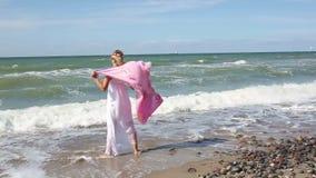 Белокурая женщина в белом платье идя на пляж с шалью в ветре сток-видео
