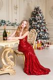 Белокурая женщина в красном платье с стеклом белого вина или шампанского распологая на стул в роскошном интерьере рождество моя в Стоковое Фото