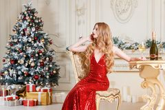 Белокурая женщина в красном платье с стеклом белого вина или шампанского распологая на стул в роскошном интерьере рождество моя в Стоковые Изображения RF