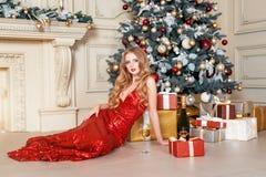 Белокурая женщина в красном платье с стеклом белого вина или шампанского в роскошном интерьере Рождественская елка, настоящие мом Стоковое фото RF