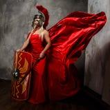 Белокурая женщина в римском красном порхая платье стоковое изображение
