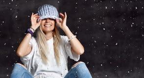 Белокурая женщина в светлом - голубое связанное усаживание шляпы счастливое усмехаясь под зимним временем снежинок стоковое изображение rf