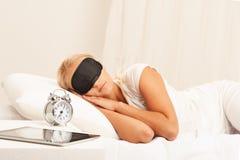 Белокурая женщина в смотреть кровати надоела на ее будильнике стоковые фотографии rf