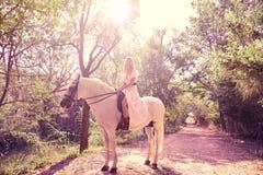 Белокурая женщина девушки ехать белая лошадь в следе Стоковое Изображение