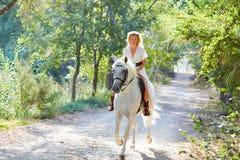 Белокурая женщина девушки ехать белая лошадь в следе Стоковые Фото