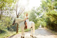 Белокурая женщина девушки ехать белая лошадь в следе Стоковое фото RF