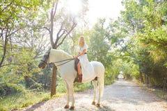 Белокурая женщина девушки ехать белая лошадь в следе Стоковые Изображения RF