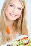 Белокурая женщина есть салат стоковое фото rf