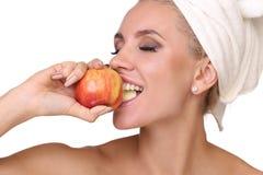 Белокурая женщина ест красное яблоко стоковые фото