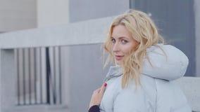 Белокурая женщина идет на улицу города в холодном солнечном дне, поворачивающ к камере и flirting, играя с волосами видеоматериал