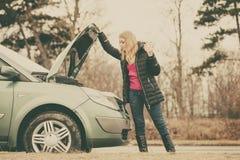 Белокурая женщина и сломанный вниз с автомобиля на дороге Стоковое Фото